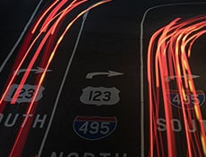 Automobile light trails over highway road sign markings