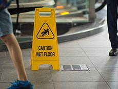 Yellow sign inside building hallway, sign showing warning of caution wet floor